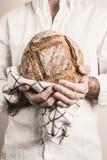 Αγροτική φλοιώδης φραντζόλα του ψωμιού στα χέρια ατόμων ` s αρτοποιών στοκ εικόνες με δικαίωμα ελεύθερης χρήσης