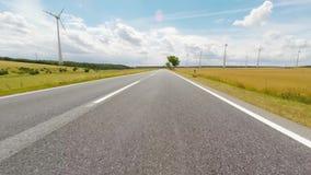 Αγροτικοί δρόμος και ανεμοστρόβιλοι απόθεμα βίντεο