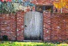Αγροτικός ξύλινος σχηματισμένος αψίδα φράκτης κήπων στο τουβλότοιχο το φθινόπωρο με τα χρωματισμένα φύλλα και το σπίτι τούβλου το στοκ εικόνα με δικαίωμα ελεύθερης χρήσης