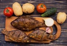 Αγροτικός πίνακας με τα τρόφιμα Τρόφιμα, σε έναν ξύλινο πίνακα Τηγανισμένα ψάρια, που μαγειρεύονται υπέροχα, πικ-νίκ Στοκ Φωτογραφίες