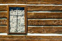 Αγροτικός τοίχος ξυλείας με ένα παράθυρο που φράσσεται από τους βράχους Στοκ Εικόνες