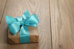 Αγροτικό κιβώτιο δώρων εγγράφου τεχνών με το μπλε τόξο κορδελλών στον ξύλινο πίνακα Στοκ Εικόνες