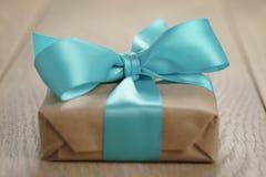 Αγροτικό κιβώτιο δώρων εγγράφου τεχνών με το μπλε τόξο κορδελλών στον ξύλινο πίνακα Στοκ φωτογραφίες με δικαίωμα ελεύθερης χρήσης