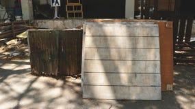 Αγροτικό ξύλινο άσπρο κενό σημάδι πινάκων με τις χρωματισμένες γραμμές και το σκουριασμένο πράσινο ζαρωμένο μέταλλο στοκ φωτογραφία με δικαίωμα ελεύθερης χρήσης