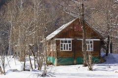 Αγροτικό ξύλινο σπίτι σε ένα χιονώδες χειμερινό δάσος Στοκ Φωτογραφίες