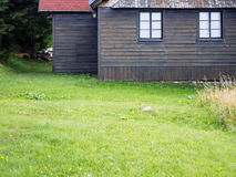 Αγροτικό ξύλινο μέτωπο εξοχικών σπιτιών βουνών με τη χλόη Στοκ εικόνες με δικαίωμα ελεύθερης χρήσης