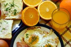 Αγροτικό πρόγευμα - ψημένο ψωμί με το βούτυρο και τα φρέσκα κρεμμύδια, τα τηγανισμένα αυγά και το μπέϊκον στοκ εικόνες