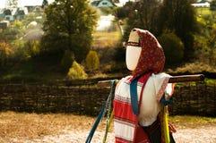 Αγροτικό σκιάχτρο ενάντια στο σκηνικό του χωριού Στοκ Εικόνα