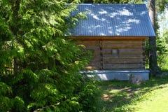 Αγροτικό σπίτι λουτρών με τα παράθυρα φιαγμένα από τοποθετημένη σε στρώματα ξυλεία καπλαμάδων θερινός θερμός καιρός Πράσινος χορτ στοκ φωτογραφία