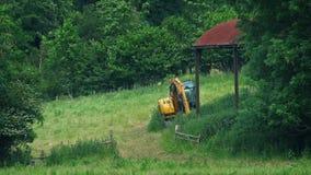 Αγροτικό τοπίο με το Digger και παλαιό υπόστεγο απόθεμα βίντεο