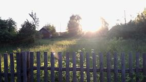 Αγροτικό τοπίο στο πίσω φως του ήλιου Παλαιός ξύλινος φράκτης, και πίσω από το ένας χορτοτάπητας φιλμ μικρού μήκους