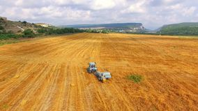 Αγροτικό τρακτέρ με το ρυμουλκό που κινείται κατά μήκος του τομέα σίτου απόθεμα βίντεο