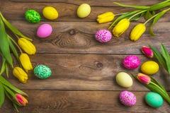 Αγροτικό υπόβαθρο Πάσχας με τα ρόδινα, κίτρινα και πράσινα χρωματισμένα αυγά στοκ φωτογραφία με δικαίωμα ελεύθερης χρήσης