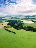 Αγροτικό υπόβαθρο τοπίων με τους τομείς εγκαταστάσεων και τα μεγαλοπρεπή σύννεφα Στοκ φωτογραφία με δικαίωμα ελεύθερης χρήσης