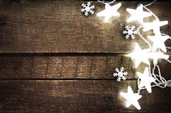 Αγροτικό υπόβαθρο Χριστουγέννων με τα φω'τα, snowflakes, τα αστέρια και το φ στοκ φωτογραφίες