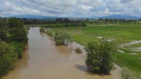 Αγροτικό χωριό κατά μήκος του νερού ποταμού στα υψηλά επίπεδα με την πλημμύρα των λιβαδιών ένας νεφελώδης ουρανός φιλμ μικρού μήκους