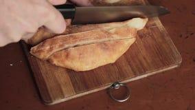 Αγροτικό ψωμί περικοπών σε έναν ξύλινο πίνακα φιλμ μικρού μήκους