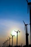 Αγρόκτημα ανεμοστροβίλων με τις ακτίνες του φωτός στο ηλιοβασίλεμα Στοκ Εικόνες