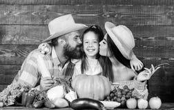 Αγρότες οικογενειακού αγροτικοί ύφους στην αγορά με τα φρούτα και την πρασινάδα λαχανικών Φεστιβάλ συγκομιδών γονέων και κορών r στοκ εικόνα