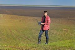 Αγρότης με το lap-top στα σπορόφυτα Στοκ Φωτογραφία