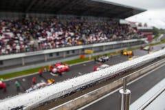Αγωνιστικά αυτοκίνητα στο αρχικό πλέγμα Η εστίαση στο κιγκλίδωμα με τη βροχή μειώνεται στοκ φωτογραφία