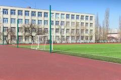Αγωνιστικός χώρος ποδοσφαίρου ποδοσφαίρου κοντά στο αστικό σχολείο Στοκ εικόνες με δικαίωμα ελεύθερης χρήσης