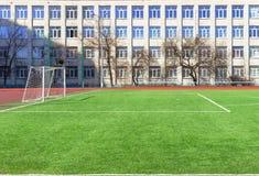 Αγωνιστικός χώρος ποδοσφαίρου ποδοσφαίρου κοντά στο σχολικό κτίριο Στοκ εικόνα με δικαίωμα ελεύθερης χρήσης
