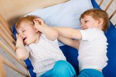 Αγόρια λίγων αμφιθαλών που έχουν τη διασκέδαση στο κρεβάτι στο σπίτι Στοκ Εικόνες