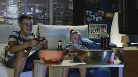Αγόρια εφήβων που παίζουν videogame μαζί στον καναπέ Στοκ Εικόνα