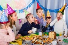 Αγόρια και κορίτσια ευτυχή να δουν το ένα το άλλο κατά τη διάρκεια του γεύματος Χριστουγέννων Στοκ Εικόνες