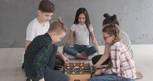 Αγόρια και κορίτσια που παίζουν foosball στο σπίτι φιλμ μικρού μήκους