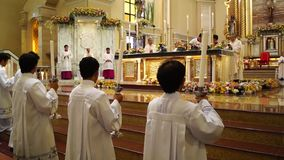 Αγόρια Μάρτιος βωμών τα κεριά τους στην εκκλησία κατά τη διάρκεια του μαζικού εορτασμού απόθεμα βίντεο