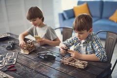 Αγόρια που κρατούν smartphones και που απολαμβάνουν ξοδεύοντας το χρόνο με τους κατασκευαστές τους στοκ εικόνες με δικαίωμα ελεύθερης χρήσης