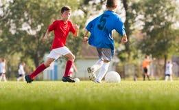 Αγόρια που παίζουν το παιχνίδι ποδοσφαίρου ποδοσφαίρου στον αθλητικό τομέα Στοκ Εικόνα