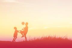 Αγόρια που παίζουν το ποδόσφαιρο στο ηλιοβασίλεμα Έννοια σκιαγραφιών Στοκ Εικόνες