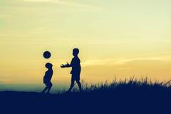 Αγόρια που παίζουν το ποδόσφαιρο στο ηλιοβασίλεμα Έννοια σκιαγραφιών Στοκ Φωτογραφία