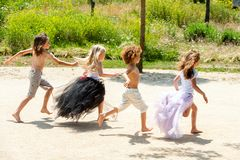 Αγόρια που χαράζουν τα κορίτσια στο πάρκο. Στοκ Φωτογραφία