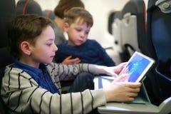 Αγόρια που χρησιμοποιούν την ταμπλέτα στο αεροπλάνο στοκ φωτογραφία με δικαίωμα ελεύθερης χρήσης