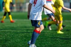 Αγόρια στο άσπρο κίτρινο sportswear τρέξιμο, dribble, επίθεση στο αγωνιστικό χώρο ποδοσφαίρου Νέοι ποδοσφαιριστές με τη σφαίρα στ στοκ φωτογραφίες
