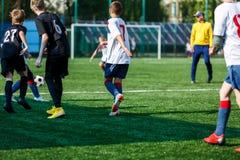 Αγόρια στο μαύρο άσπρο sportswear τρέξιμο, dribble, επίθεση στο αγωνιστικό χώρο ποδοσφαίρου Νέοι ποδοσφαιριστές με τη σφαίρα στην στοκ εικόνα με δικαίωμα ελεύθερης χρήσης