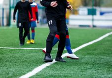 Αγόρια στο μαύρο κόκκινο sportswear τρέξιμο, dribble, επίθεση στο αγωνιστικό χώρο ποδοσφαίρου Νέοι ποδοσφαιριστές με τη σφαίρα στ στοκ εικόνες με δικαίωμα ελεύθερης χρήσης