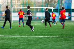 Αγόρια στο μαύρο κόκκινο sportswear τρέξιμο, dribble, επίθεση στο αγωνιστικό χώρο ποδοσφαίρου Νέοι ποδοσφαιριστές με τη σφαίρα στ στοκ εικόνα με δικαίωμα ελεύθερης χρήσης