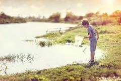 Αγόρι από έναν ποταμό με ένα δίχτυ του ψαρέματος στο θερινό ήλιο Στοκ Εικόνες
