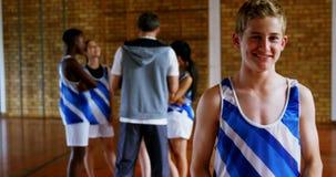 Αγόρι γυμνασίου που στέκεται στο γήπεδο μπάσκετ 4k απόθεμα βίντεο