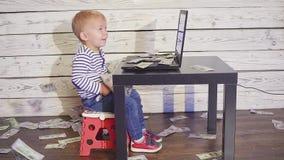 Αγόρι δύο ετών παιδιών με έναν υπολογιστή και μειωμένα χρήματα συνεδρίαση αγοριών χαμόγελου στον πίνακα με τα τραπεζογραμμάτια la απόθεμα βίντεο