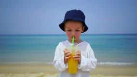 Αγόρι δύο ετών που πίνει το μάγκο φρέσκο στην παραλία στο υπόβαθρο του ωκεανού φιλμ μικρού μήκους