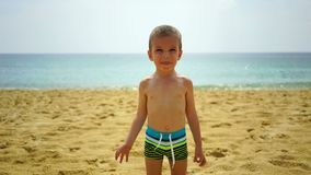Αγόρι δύο ετών που παίζουν στην παραλία κοντά στον ωκεανό φιλμ μικρού μήκους