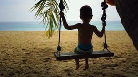 Αγόρι δύο ετών ταλάντευσης σε μια ταλάντευση στην παραλία κοντά στον ωκεανό απόθεμα βίντεο