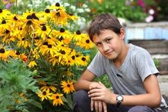 Αγόρι ενάντια στο θερινό λουλούδι Στοκ εικόνα με δικαίωμα ελεύθερης χρήσης