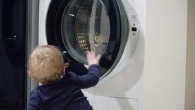 Αγόρι ενός έτους βρεφών αγοράκι που φαίνεται πλυντήριο στο σπίτι Ζητήματα εγχώριων συσκευών Το αγοράκι κλείνει το πλυντήριο απόθεμα βίντεο